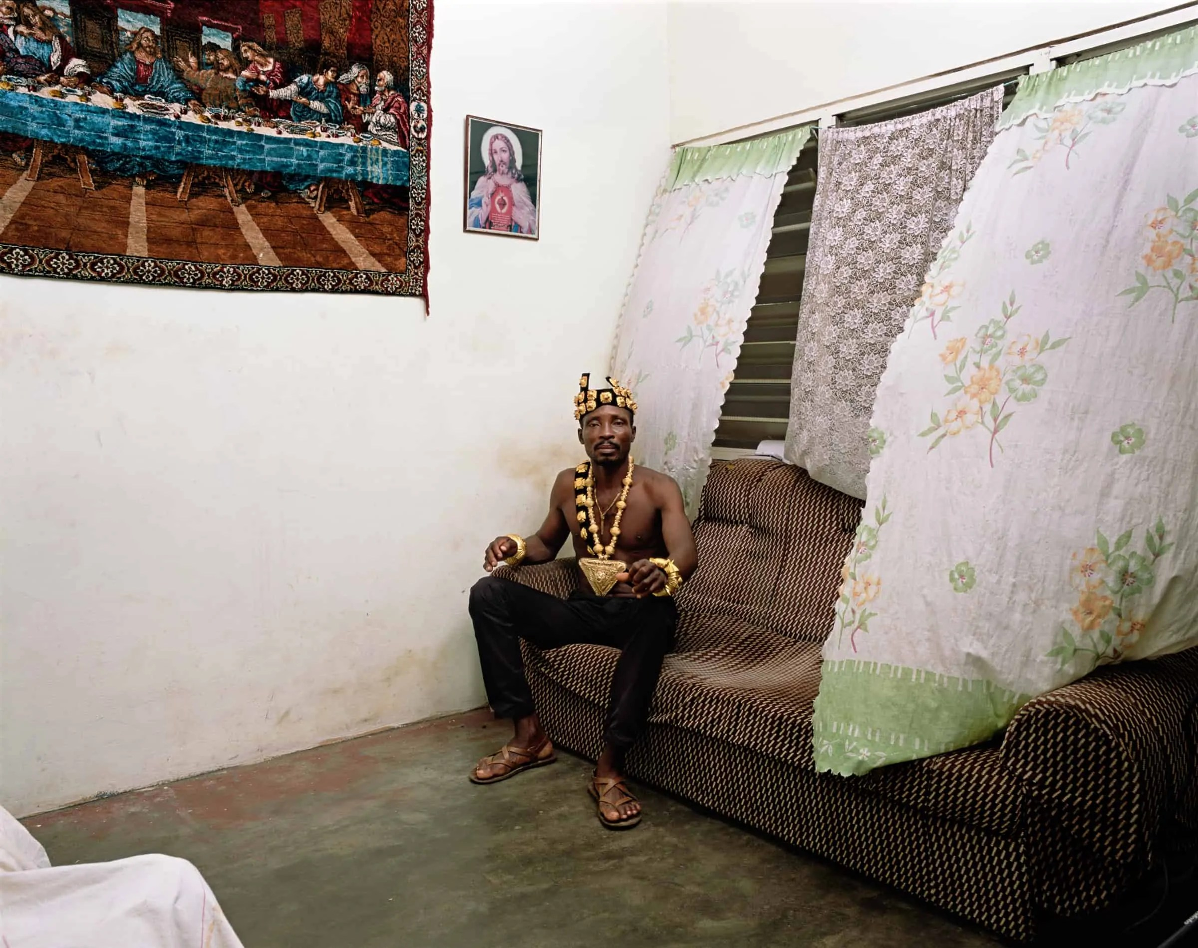 Man in a crown sits on couch photographed by Deana Lawson
