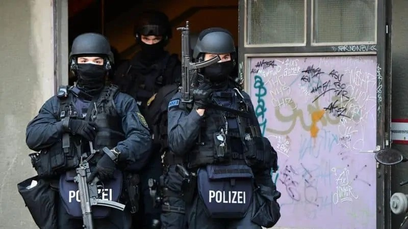 Three police in full gear carry guns as they carry out raids in Berlin searching for information on the Green Vault heist