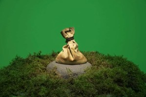 A bag of sand sits atop a stone surrounded by moss against a green backdrop by Divya Mehra