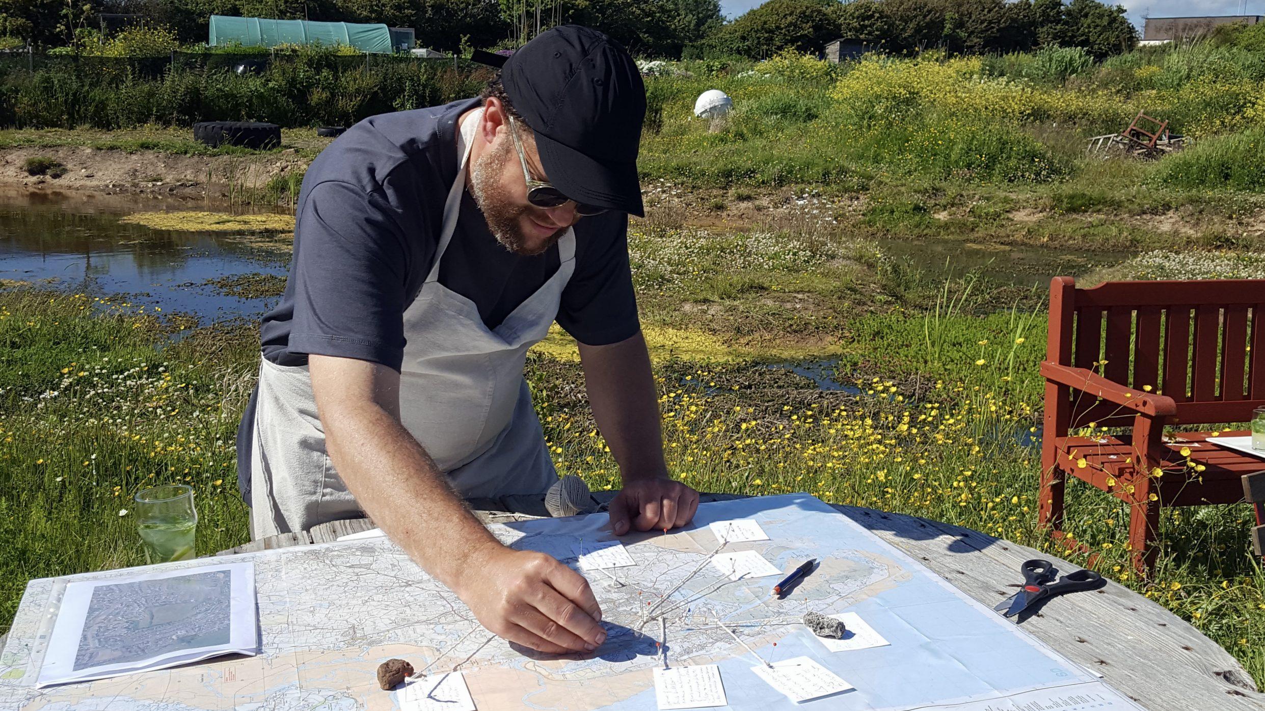 Image: Artist Owen Griffiths places pins, string and hand written notes on a map of Barrow.