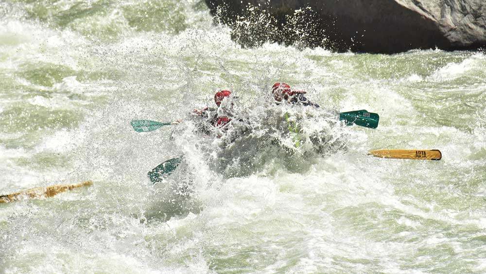 an oar-paddle raft gets wet in Split Rock rapid while whitewater rafting on the Merced River in California with ARTA river trips
