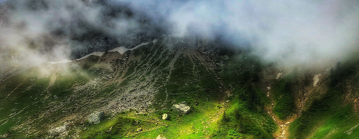 Photograph of a green land from overhead. Clouds creep in from the top of the image.