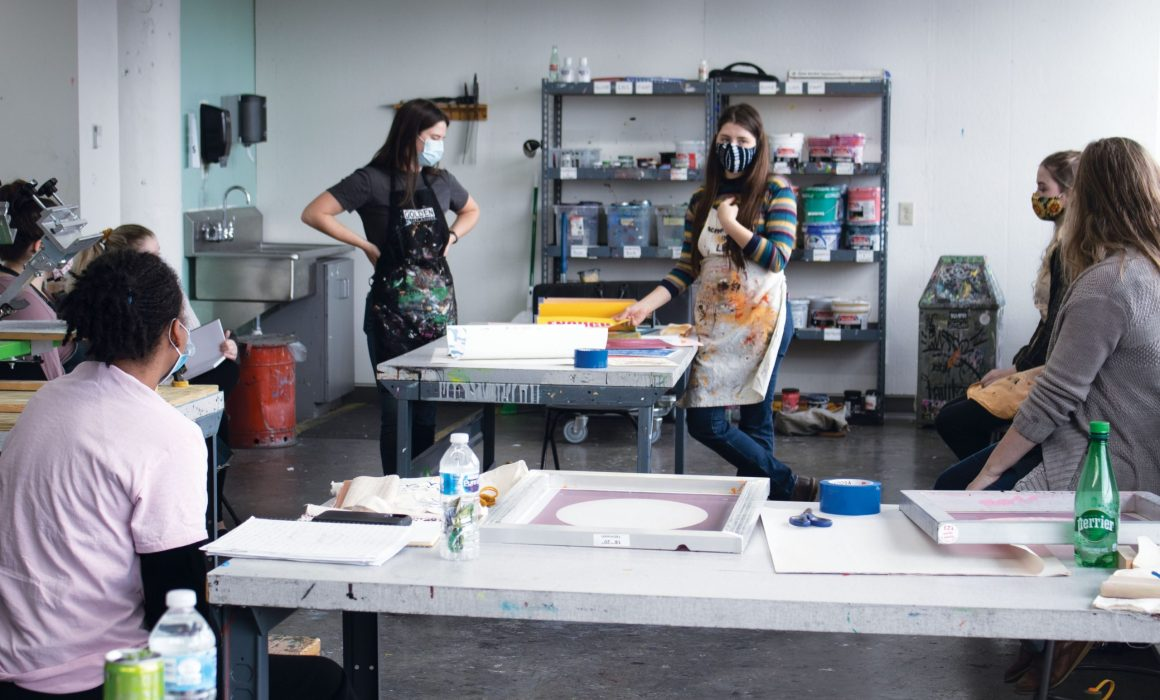 A photo of the AAC print lab where Pull Club is teaching a group of women from OPCA,