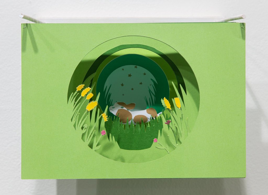 A shadow box depicting a cow in grass.