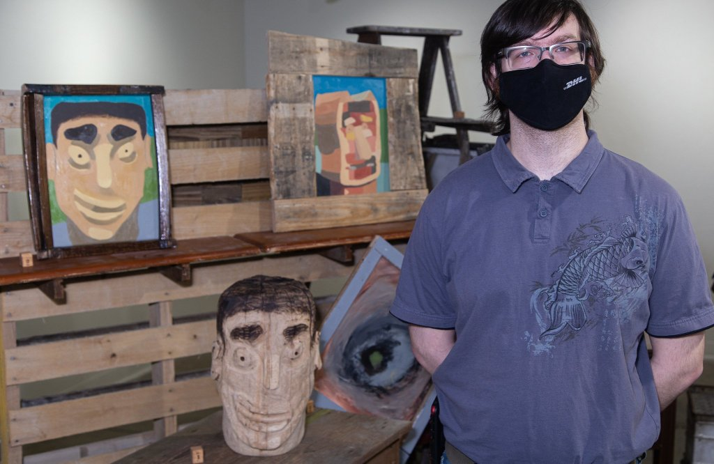 A photo of Trenton Buck standing in front of his work.