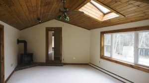 Family room with gas stove, skylight and cathedral ceiling leads to the entrance to the master suite