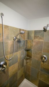 Slate and glass walk-in shower with dual shower heads.