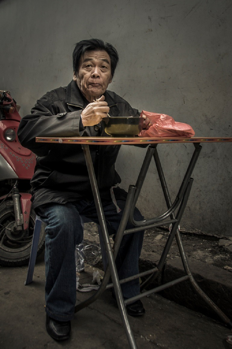 Image- A well dressed man eats on a desk. Behind him is a Vesper. Ron Gessel, Man Eating, 'The Streets of Shanghai'.