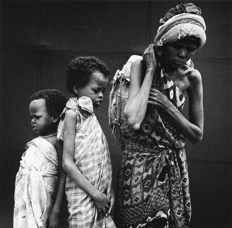 Image:  It shows a Somali Refugee Family made up of three children. It shows the consequences of war and natural desaters. It was taken by Hans Gedda, a professional photographer who captures intimate emotions