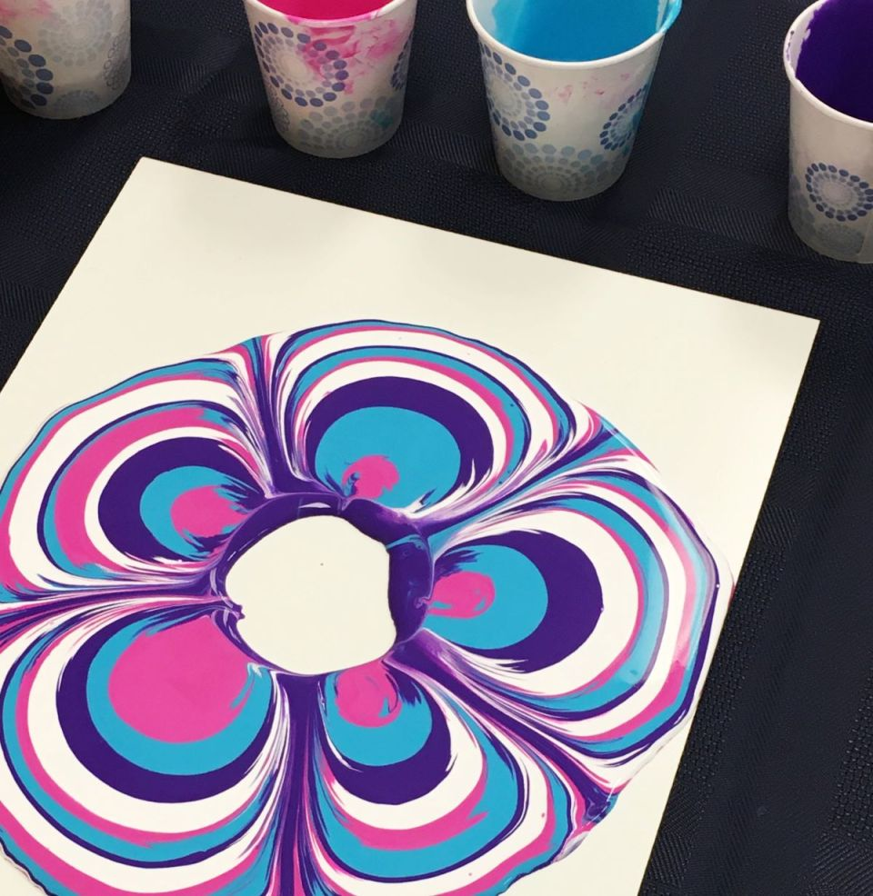 Acrylic paint-pouring activity with pink, blue and white marbled effect