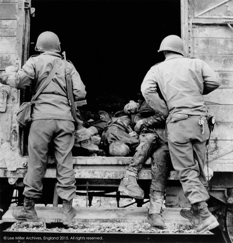 5_US soldiers examine a rail truck loaded with dead prisoners, Dachau, Germany, 1945, 76-15