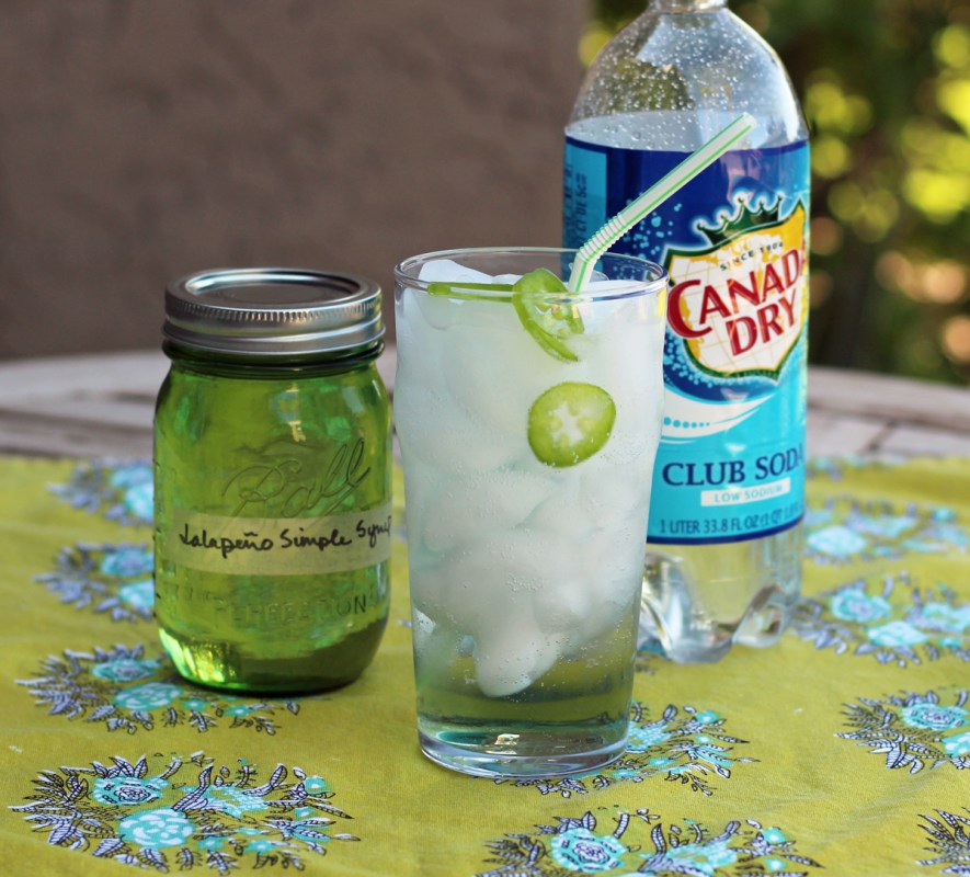 A glass of homemade jalapeno soda, a mason jar of jalapeno simple syrup and club soda on a green tablecloth.
