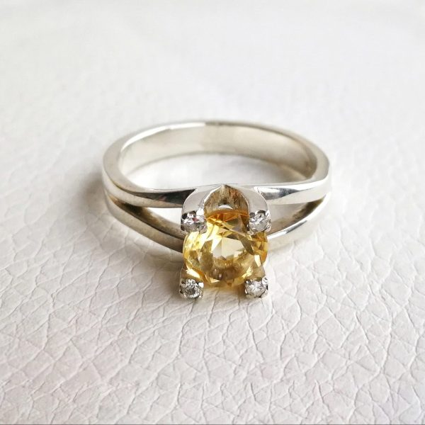 sterling silver ring with a splitted shank on top forming the setting. A citrine is set in between the big prongs and a diamond is set on top of each prongs.