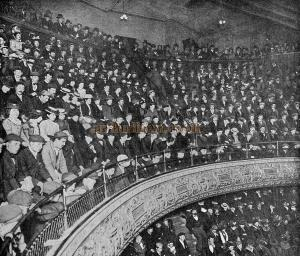 """A Typical Music Hall Gallery. The photograph was taken at the """"London"""" Music Hall, Shoreditch; the audience, who, at the time, were enjoying a chorus song, were not warned of the fact. - From 'The Playgoer' 1901 - Courtesy Iain Wotherspoon. - Click to Enlarge."""