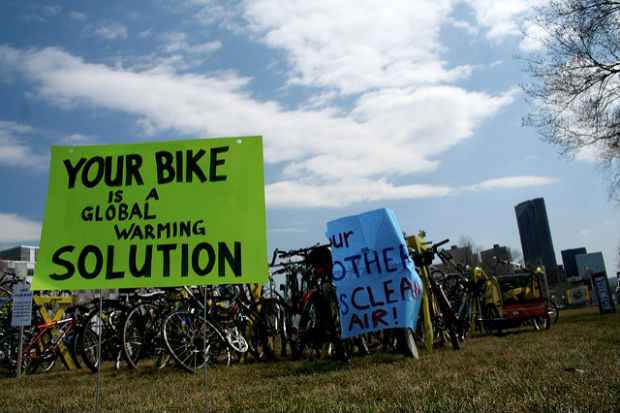 """carbon neutral: parked bikes with sign reading """"your bike is a global warming solution"""""""
