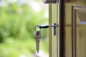 The keys in the lock of an open house door.