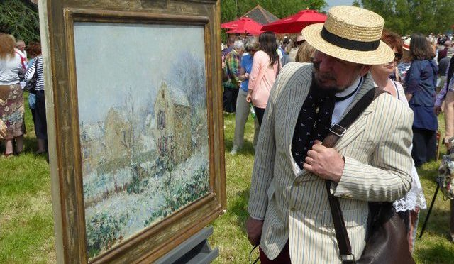Man looking at fine art painting at antique sale