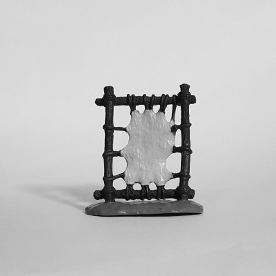 Greyscale image of a toy model of a Native American leather drying rack