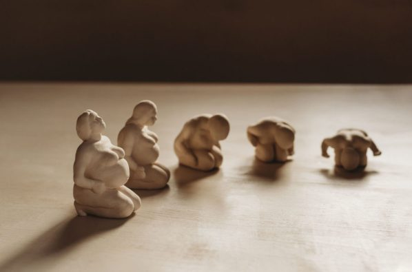 A piece of art made of 5 sculpted female figures who are pregnant. They are all kneeling, but each figure leans over her belly progressively in this installation. They are photographed on a neutral color table with natural light and with a dark background. The figures are the color of the grey clay used to sculpt them.