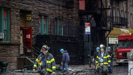 Firefighters leave a building that house