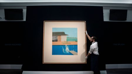 A Sotheby's employee adjusts a painting