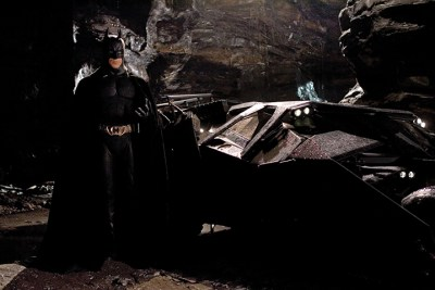 Batman stands beside his wrecked Batmobile in the shadows of the Batcave