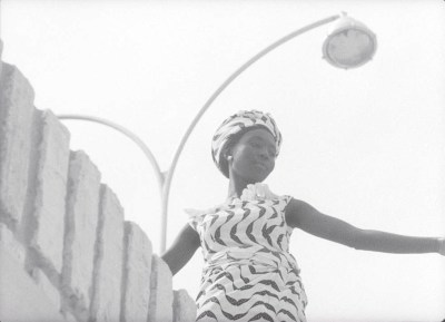 A Black woman, seem from a dramatic upward tilted angle, looks to her left. She's wearing a striking striped dress and a matching hat