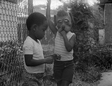 Two dark-skinned children stand in a yard by a chain-link fence. One wears a dog mask.