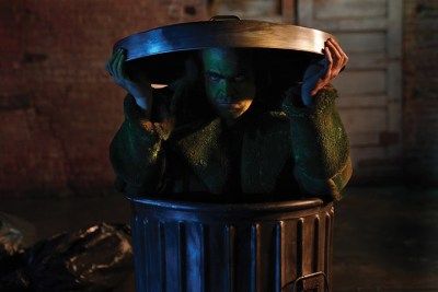 A man in green face paint and a woolly green coat frowns grouchily as he emerges from a garbage can on a dim street