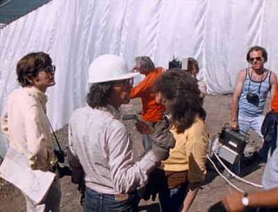Still from 'Running Fence' (1977). The artist Christo, wearing a construction helmet, guides workers around him in the creation of an artwork.