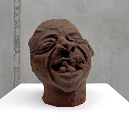 A bust made of chocolate depicting a heavily lined face with a jumble of teeth in the open mouth