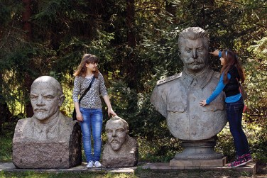 Two girls play with statues of Soviet leaders; one sticks her finger in Stalin's ear