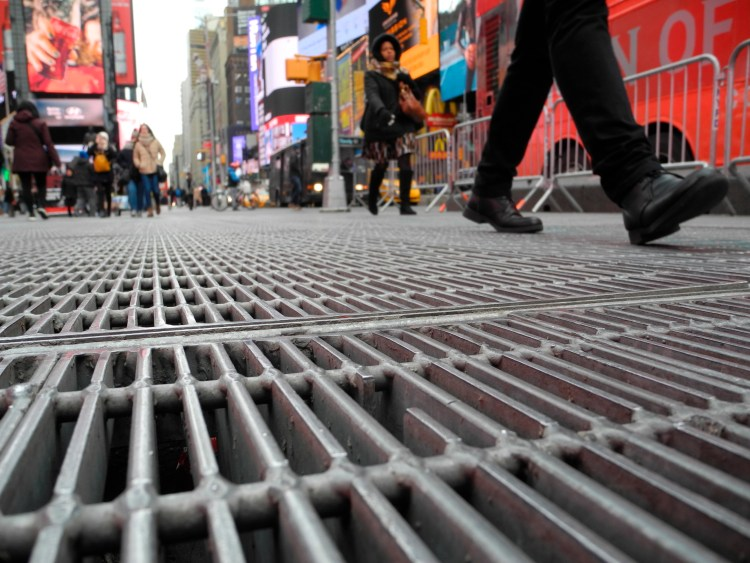 1 February 2018, USA, New York: Pedestrians walk over grids under which a sound installation of the US artist Max Neuhaus is placed, between 45th and 46th Street as well as Broadway and 7th Avenue, to be precise. The hidden art installation at one of the most famous places in the world remains undiscovered by most. A menacing growl emanates from the underground duct, 24 hours a day, seven days a week. Photo by: Johannes Schmitt-Tegge/picture-alliance/dpa/AP Images