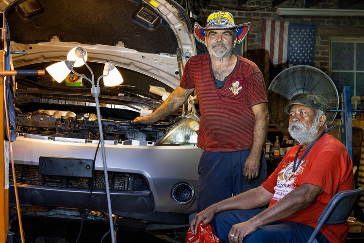 two men in a garage working on a car engine