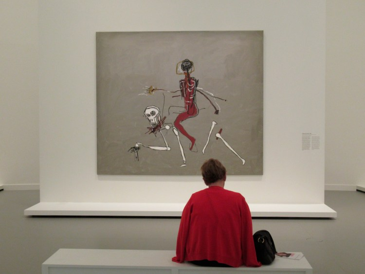 """A visitor in front of the """"Riding with Death"""" by Jean-Michel Basquiat."""