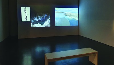 In a gallery, a bench is placed in front of three projected images of maps.