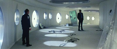 Two men in suits stand in a retrofuturist building with circular windows. There is stuff on the floor that looks like cables or equipment.