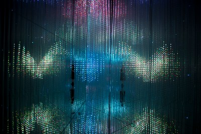 The refracted silhouettes of two people can be seen in an installation of colored lights that radiate through a gridded structure