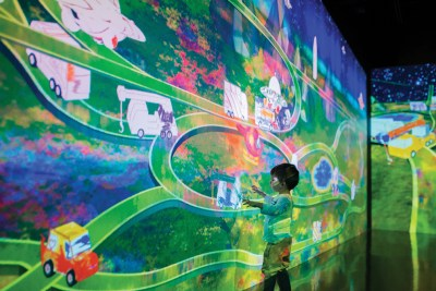A child interacts with a wall-size projection of trucks and cars traveling a winding green highway