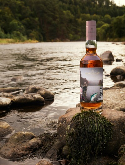 One of the bottles from Anecdotes of Ages Collection, a collaboration between Sir Peter Blake and The Macallan. The bottle is photographed on a rock, in front of a river..