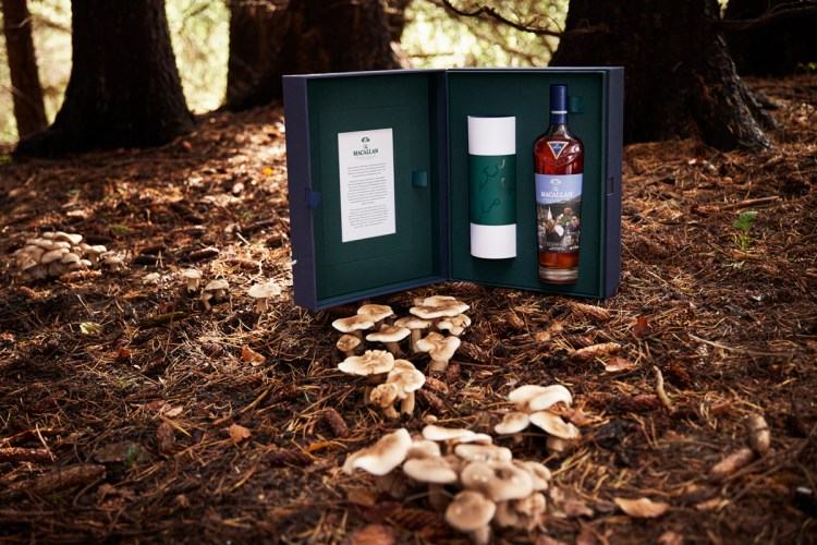 An Estate, A Community, and A Distillery whisky, in its custom box, photographed in the woods in front of mushrooms.