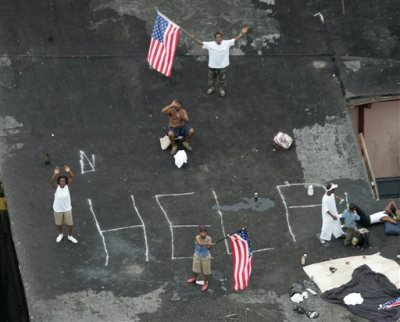 """Black people on a roof h ave written """"HELP"""" in chalk and are photographed from a plane or hellicopter. Two are waving American flags."""