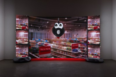 A projection screen shows a surveillance camera, animated to look like a singing face, overlooking a grocery store