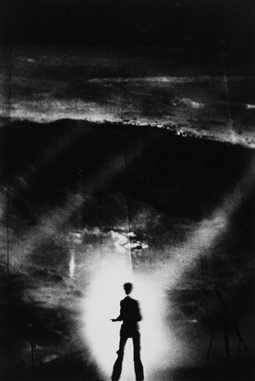 A figure appears silhouetted against illuminated mist on an otherwise darkened stage