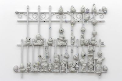 A white fence with curly metal shapes has a bunch of cute white figurines stuck on it.