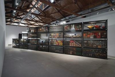 Een stapel grote stalen schanskorven is diagonaal opgesteld in een grote galerij; de schanskorven bevatten bouwmarktproducten.