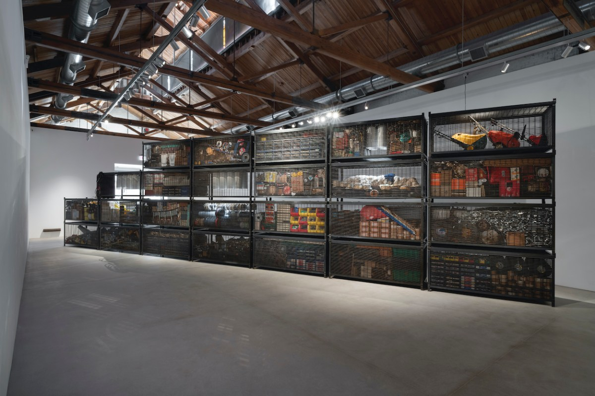 A stack of large steel gabions is arranged along a diagonal in a large gallery; the gabions contain hardware store products.