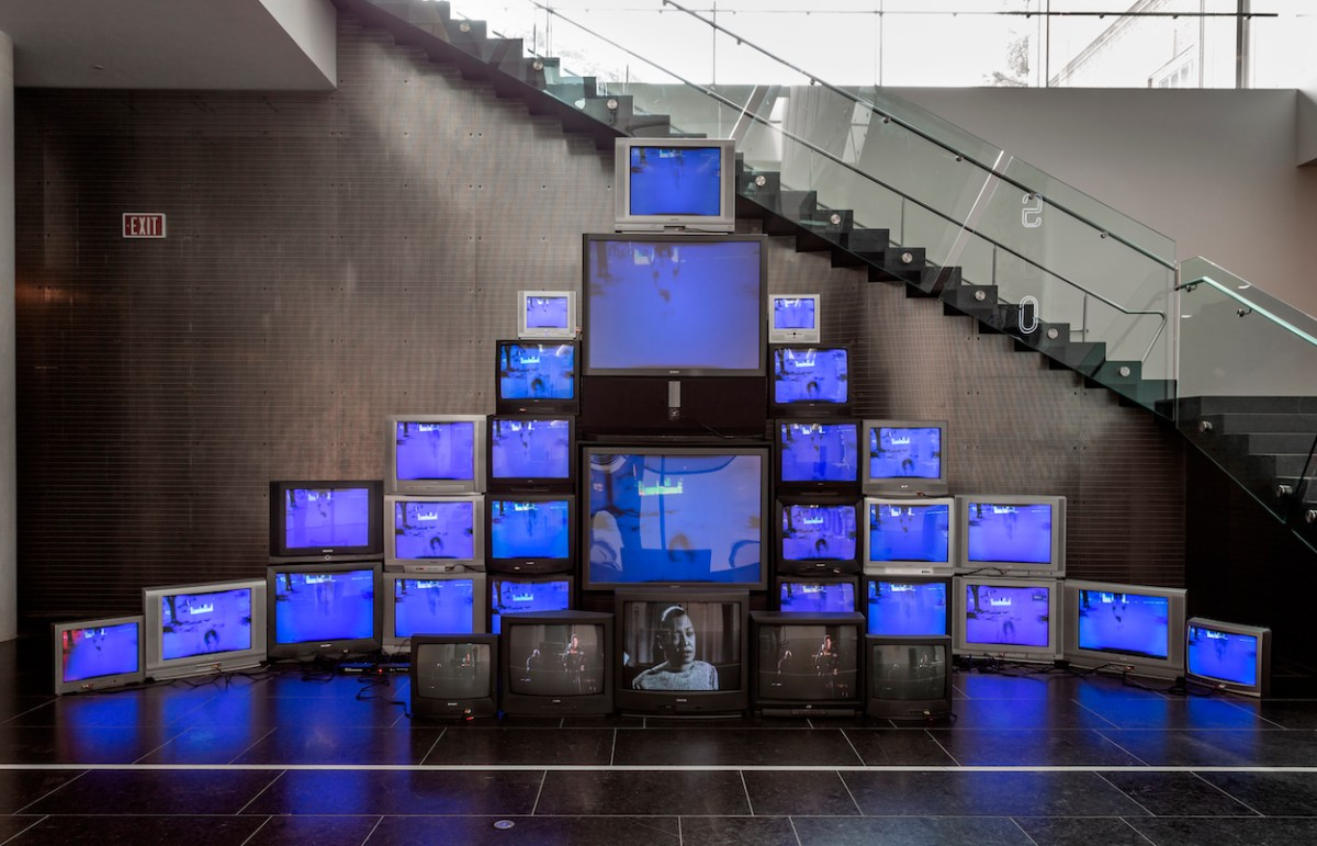 A group of tube televisions are stacked into an altar-like arrangement; all of the screens are blue except for this at the bottom. The central screen shows the face of Billie Holiday.
