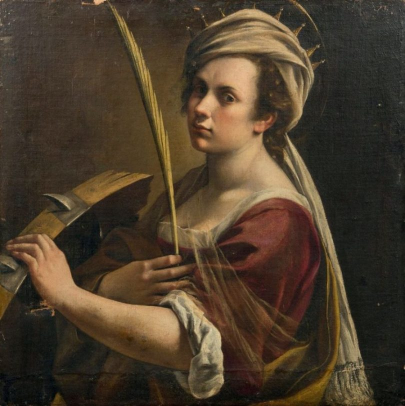 A young woman wearing a red shirt with one hand holding a palm frond and the other on a spiked torture wheel.