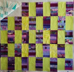 Purple strip donation quilt with yellow-green